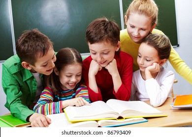 Portrait of friendly group reading book in classroom