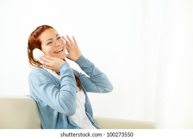 Portrait of a friendly and happy young woman listening to music at home