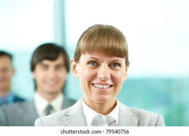 Portrait of friendly leader looking at camera with partners behind