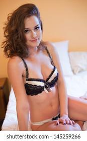 Portrait of friendly lingerie beauty posing on bed.