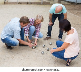 Portrait of friendly mature couples playing petanque at leisure