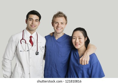 Portrait of friendly medical team standing over gray background