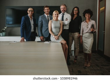 Portrait of friendly multiracial team of business professionals together in boardroom. Team of corporate business professionals looking at camera and smiling in conference room.