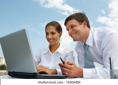 Portrait of friendly people looking at laptop monitor while working at new project