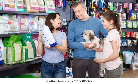 Portrait of friendly positive glad family with their puppy during visit of pet shop