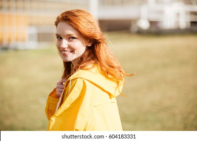 Portrait of a friendly pretty ginger hair girl in coat outdoors