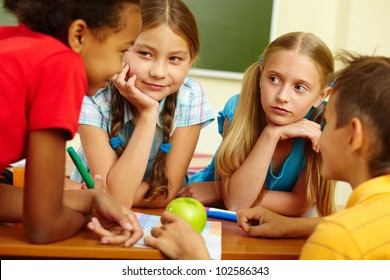 Portrait of friendly schoolchildren chatting in classroom