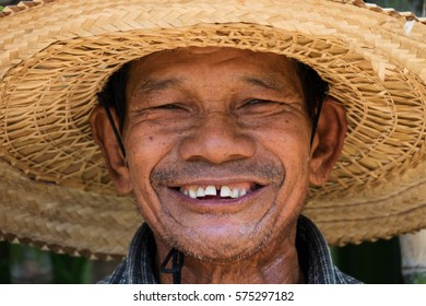 Portrait of friendly senior asian adult man with straw hat