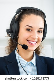 Portrait of friendly smiling  attractive young woman with headset answering call in office