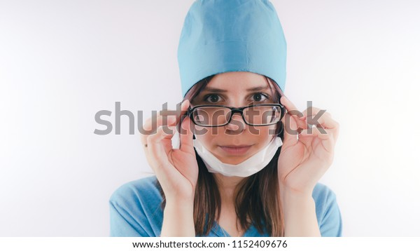 Portrait of a friendly smiling doctor woman or nurse in white medical uniform,  isolated on white background with copy space. Healthcare and medicine concept