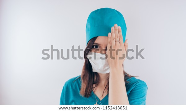 "Portrait of a friendly smiling doctor woman or nurse in white medical uniform. Hand closed one eye, the concept of ""vision check"", isolated on white background with copy space. Healthcare and medicine"