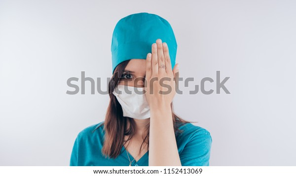 """Portrait of a friendly smiling doctor woman or nurse in white medical uniform. Hand closed one eye, the concept of """"vision check"""", isolated on white background with copy space. Healthcare and medicine"""