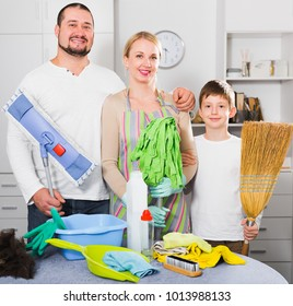 Portrait of friendly smiling family standing at room ready to clean house