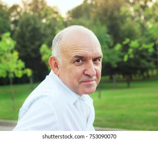 Portrait of friendly smiling senior man at summer evening