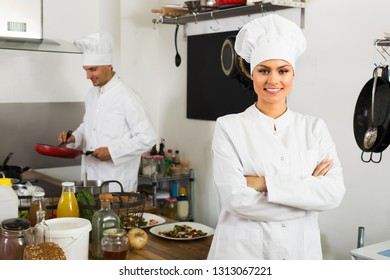 portrait of friendly smiling young woman dressed as chef standing at cafe's kitchen