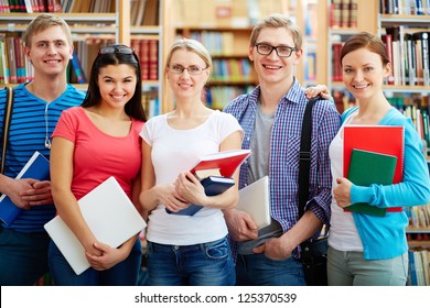 Portrait of friendly students looking at camera in college library