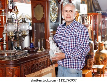 Portrait of  friendly  successful owner of antiques shop among vintage things