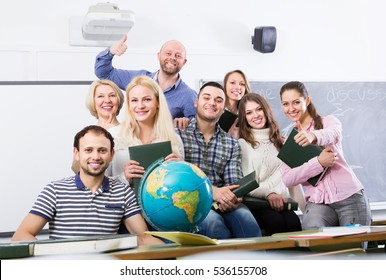 Portrait of friendly teacher and adult smiling students in classroom