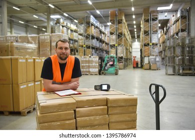portrait of friendly warehouse worker in a forwarding agency - interior with forklift - transport and storage of goods