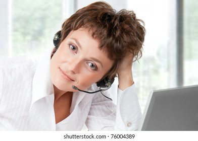 Portrait of a friendly woman with headset at her office