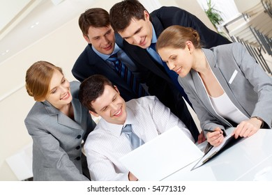 Portrait of friendly workteam looking at laptop monitor at meeting
