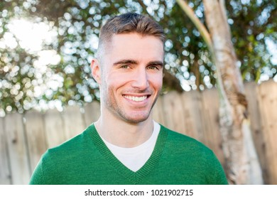 Portrait of friendly young man outside
