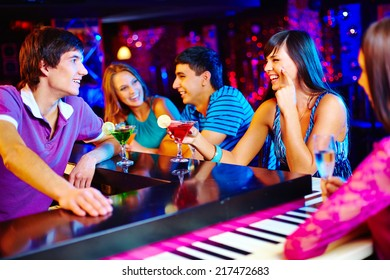 Portrait of friendly young people having cocktails in the bar