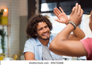 Portrait of friends giving high five at cafe while having lunch. Young guys friends giving a high five, slapping each others hand in congratulations while sitting in cafeteria.