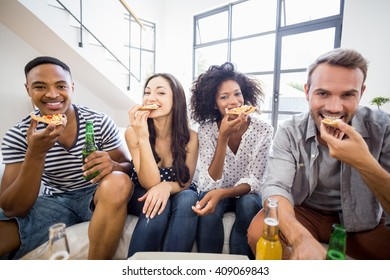Portrait of friends having a pizza in living room