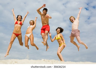 Portrait of friends in high jump over sandy shore against cloudy sky