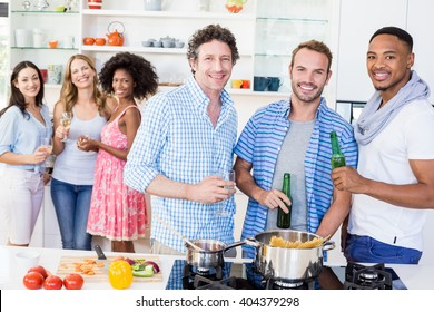 Portrait of friends holding beer bottles and glasses of wine in kitchen at home