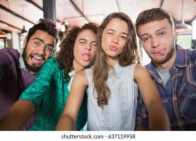 Portrait of friends making face in restaurant