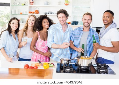 Portrait of friends standing together and holding beer bottles and glasses of wine in kitchen