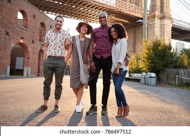 Portrait Of Friends Walking By Brooklyn Bridge In New York City