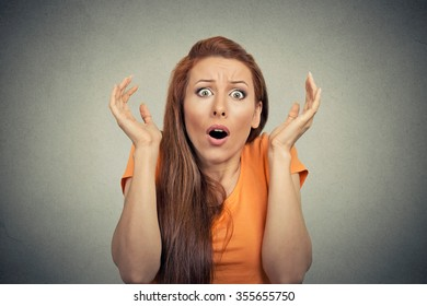 Portrait frightened shocked scared woman looking at camera isolated on gray wall background. Human emotion facial expression body language unexpected reaction
