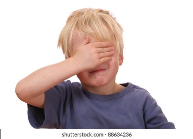 Portrait of a frightened young boy covering his eyes