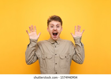 Portrait of frightened young man in glasses and shirt on yellow background, raised his hands in fear and looks into camera with shocked face. Scared boy nerd looks into camera with shocked face.