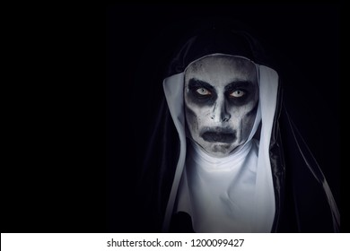 portrait of a frightening evil nun, wearing a typical black and white habit, against a black background, with some blank space on the left