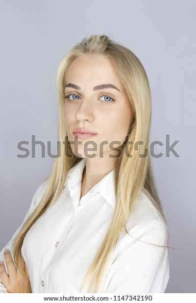 portrait in front of a blonde girl with long hair and elegant perfect eyebrows. easy make-up and white shirt. perfect clean even skin. in her eyes a glare from a circular flash