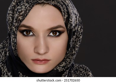 Portrait of a front view of a beautiful arab woman face with a head scarf on a gray background