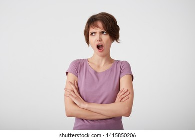 Portrait of frowning displeased short-haired lady in blank t-shirt, outraged by the gossip she heard from a friend, stands over white wall with arms crossed.