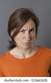 portrait of frowning middle aged woman having doubts and concerns, complaining and grumbling with irritation and exasperation, grey background
