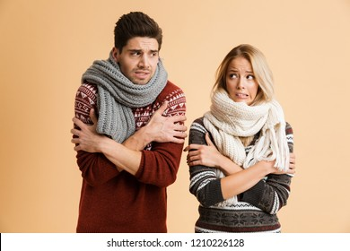 Portrait of a frozen young couple dressed in sweaters and scarves standing together isolated over beige background, shaking, looking at each other