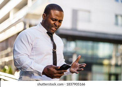Portrait of frustrated african-american businessman who is using smartphone.