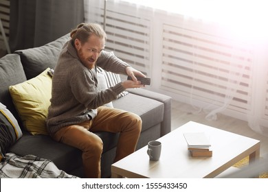 Portrait of frustrated bearded man watching TV at home and trying to switch channels via remote control, copy space
