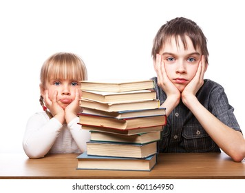 Portrait of frustrated boy and girl sitting at a desk with pile of books holding heads having learnind problems