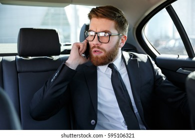 Portrait of a frustrated business man in eyeglasses talking on mobile phone while sitting in the back seat of car
