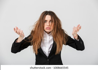 Portrait of a frustrated businesswoman dressed in suit pulling her hair out isolated over gray background