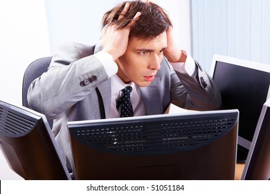 Portrait of frustrated employer surrounded by computers with his hands on head