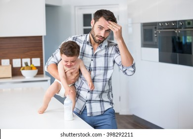 Portrait of frustrated father holding crying baby boy by table at home